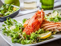 Boiled lobster with salad and wine cup. Фото trexec - Depositphotos
