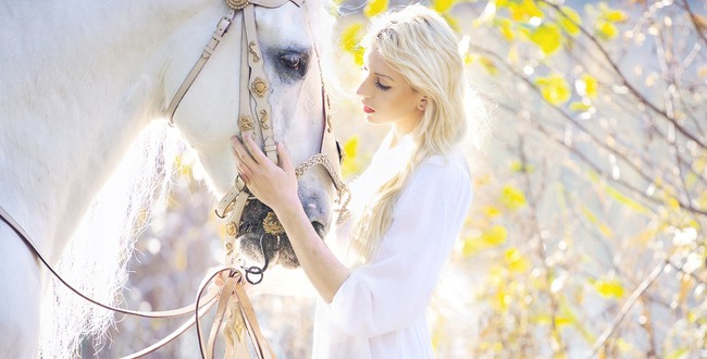 Красивые девушки Конрада Бака. Attractive blonde cutie touching royal horse. Фото konradbak - Depositphotos