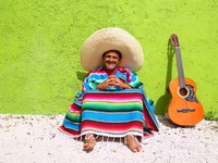 Мексика. Mexican typical lazy topic man guitar poncho sit. Фото lunamarina - Depositphotos