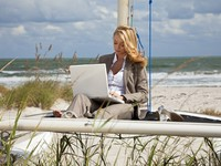 Beautiful Young Woman Using Laptop On Boat At The Beach. Фото Darren Baker - Depositphotos