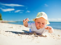 Little toddler on the beach exploring sand. Фото mvaligursky - Depositphotos