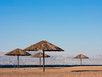 Иордания. Sunshades near on beach of the Read Sea in Aqaba, Jordan. City of Eilat, Egypt in background. vkovalcik - Depositphotos