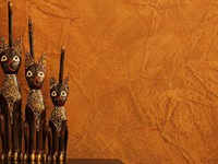Three carved wooden cats against faux finish wall. фото Alexander Sviridov - Depositphotos