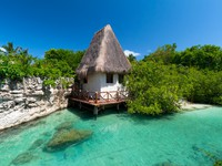 Idyllic mexican jungle scenery with hut on the water. Фото Patryk Kosmider - Depositphotos