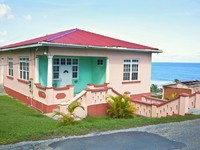 Барбадос. Bright pastel hues of a cement block Caribbean house on a hill top in rural Barbados. Фото Verena Matthew - Depositphotos