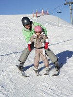 Обучение катанию на лыжах. Father Teaching Daughter To Ski Whilst On Holiday In Mountains. Фото monkeybusiness - Depositphotos