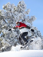 Панорама горнолыжного курорта. Man performing jump on snowboard. Фото photography33 - Depositphotos