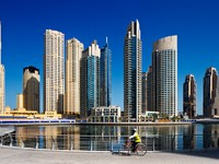 ОАЭ. Дубай Марина. A cyclist cycles the Marina walk, Dubai Marina and JBR. Фото Sophie_James - Depositphotos