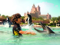ОАЭ. Дубай. Atlantis, The Palm - Marine & Waterpark - Dolphin Bay - Boy with Dolphins