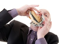 Greed avarice consuming dollars. Фото Tracy Nors - Depositphotos