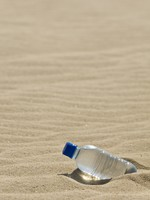 Bottle of Water In A Desert of Sand. Фото Darren Baker - Depositphotos