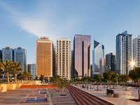 ОАЭ. Абу Даби. A warm sun illuminates the Abu Dhabi Skyline. Фото Sophie_James - Depositphotos