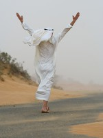 ОАЭ. Абу Даби. Arab man walking in sand storm. Фото Sergey Rusakov - Depositphotos