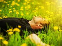 Мечта. Man lying on grass at sunny day. Фото katalinks - Depositphotos