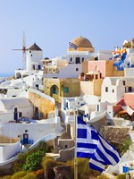 Греция. Санторини. Santorini view (Oia) and greek flag. Фото Violin - Depositphotos