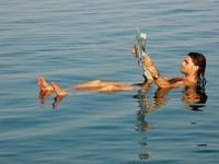 Израиль. Мертвое море. Man floating in a dead sea with newspaper. Фото bhairav -Depositphotos