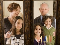 Grandparents and grandchildren with hannukkia, at the window. Фото Noam Armonn - Depositphotos