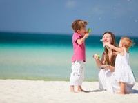 Мальдивы. Mother and kids having fun on beach. Фото shalamov - Depositphotos