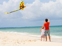 Мальдивы. Maldives. Father and son flying kite on beach. Фото shalamov - Depositphotos