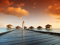 Мальдивы. Woman in a dress on maldivian sunset. Фото yellow2j - Depositphotos