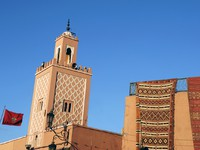 Марокко. Марракеш. Minaret of a mosque with Moroccan national flag in Marrakesh. Фото Robert paul Van beets - Depositphotos