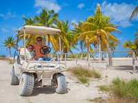 Мексика. Ривьера Майя. Dad with his two daughters driving golf cart at tropical country. Фото d.travnikov - Depositphotos