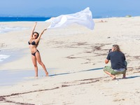 Мексика. Ривьера Майя. Professional photographer working with a model on the beach. Фото netfalls - Depositphotos