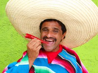Мексика. Mexican man poncho sombrero eating red hot chili. Фото lunamarina - Depositphotos
