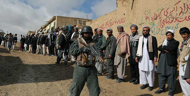 An Afghan policeman keeps watch as Afghan voters line up to vote at a local polling station in Ghazni on April 5, 2014. Фото - AFP, Rahmatullah Alizadah