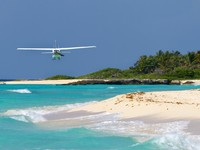Small tourist plane over Caribbean beach in Mexico. Фото - Depositphotos